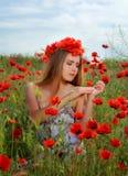 Девушка идя в поле мака Стоковое Изображение RF