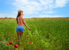 Девушка идя в поле мака Стоковая Фотография