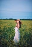 Девушка идя в поле на заходе солнца Стоковые Фото