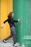 Девушка идя около красочные стены Стоковое Фото