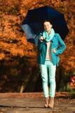 Девушка идя с голубым зонтиком в осеннем парке Стоковое фото RF