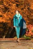 Девушка идя с голубым зонтиком в осеннем парке Стоковые Изображения