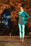 Девушка идя с голубым зонтиком в осеннем парке Стоковое Изображение