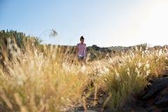 Девушка идя через очень длинную траву Стоковые Фото