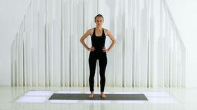 Девушка йоги в черном платье стоит в белой студии акции видеоматериалы