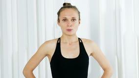 Девушка йоги в черном платье стоит в белой студии сток-видео