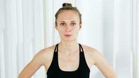 Девушка йоги в черном платье стоит в белой студии видеоматериал