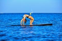 Девушка йоги над МАЛЕНЬКИМ ГЛОТКОМ стоит вверх доска прибоя Стоковые Изображения