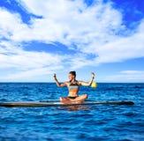 Девушка йоги над МАЛЕНЬКИМ ГЛОТКОМ стоит вверх доска прибоя Стоковое Изображение RF