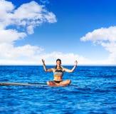 Девушка йоги над МАЛЕНЬКИМ ГЛОТКОМ стоит вверх доска прибоя Стоковая Фотография