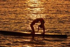 Девушка йоги над МАЛЕНЬКИМ ГЛОТКОМ стоит вверх доска прибоя Стоковая Фотография RF