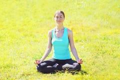 Девушка йоги размышляет сидеть на лотосе представления травы в летнем дне Стоковое Фото