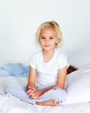 девушка камеры кровати немногая смотря сидящ Стоковое Фото