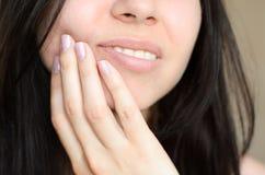 Девушка касается ее стороне из-за toothache Стоковые Фото