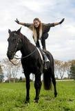 Девушка катания и черный жеребец стоковые изображения rf
