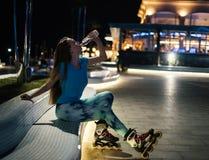 Девушка кататься на коньках ролика питьевая вода от пластичной бутылки Стоковые Фото