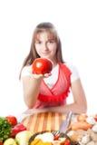 Девушка кашевар предлагает томат стоковое изображение