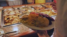 Девушка кладет ее мясные блюда на плиту на гостинице во время обеда сток-видео