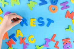 Девушка кладет из пестротканых писем остатки слов Красивейшая предпосылка Стоковое Изображение RF