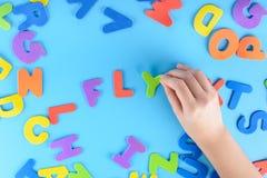 Девушка кладет из пестротканых писем слова летают Красивейшая предпосылка Стоковое фото RF