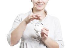 Девушка кладет монетку в копилке Соберите и сдержите деньги дома Концепция копилки и монеток Женщина с копилкой и монеткой стоковые фотографии rf
