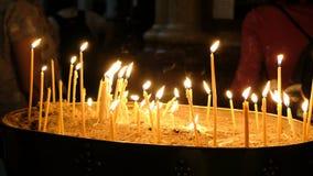 Девушка кладет свечу горя в церковь в темноте против фона людей Подсвечник песка сток-видео