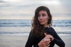 Девушка кладет цинк перед серфингом Близкая поднимающая вверх съемка красивой девушки с розовой маской цинка zurf, одетая в черно стоковые изображения rf
