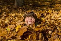 Девушка кладя в цветастые листья Стоковые Изображения