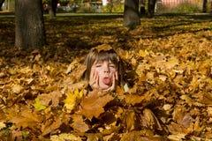 Девушка кладя в цветастые листья Стоковые Фотографии RF