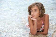 девушка кладя wate моря подростковое стоковое фото rf