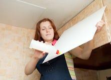 Девушка клеит плитку потолка стоковые изображения rf