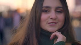 Девушка конца-вверх художественная кавказская с красивым длинным коричневым цветом смотрит холодок камеры и спокойно стоит в горо сток-видео