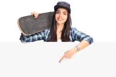 Девушка конькобежца держа указывать на шильдик Стоковое фото RF