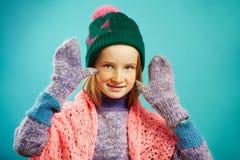 Девушка красивого ребенка носит mittens зимы, теплый свитер, шляпу с pompom и openwork шарф накидки на изолированной сини стоковые фотографии rf