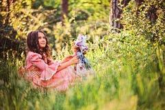 Девушка красивого ребенка одетая как принцесса сказки играя с куклой в лесе лета Стоковые Изображения
