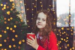 Девушка красивого ребенка сидя с чашкой кофе окном Стоковое Изображение RF