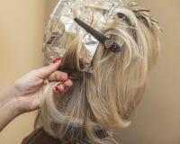 Девушка красит волосы в салоне красоты на парикмахере Стоковое Фото