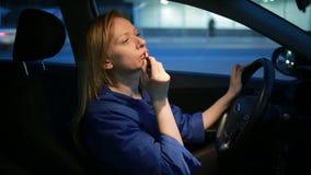 Девушка красит губы при лоск губы, сидя за рулем автомобиля