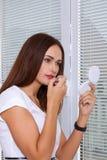 Девушка красит губы с губной помадой Стоковое Изображение