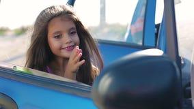 Девушка красит лоск губы в зеркале видеоматериал