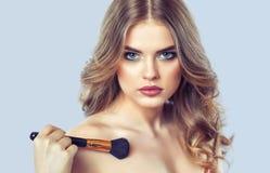 Девушка красит порошок на стороне и тело, завершает глаза smokey макетирует в салоне красоты стоковая фотография rf
