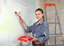 Девушка красит стену с роликом стоковые изображения rf