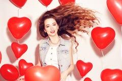Девушка красоты Валентайн с красными воздушными шарами смеясь, на белой предпосылке красивейшие счастливые детеныши женщины День  стоковое изображение