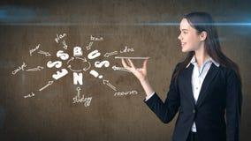 Девушка красоты в костюме держа незримый поднос при copyspace стоя близко стена с эскизом идеи дела нарисованная на ем Стоковые Изображения RF