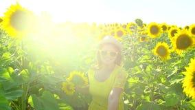 Девушка красоты при длинные красные волосы бежать на желтом поле солнцецвета, поднимая руки счастливая женщина outdoors teen подр видеоматериал