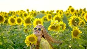 Девушка красоты при длинные красные волосы бежать на желтом поле солнцецвета, поднимая руки счастливая женщина outdoors teen подр сток-видео