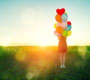 Девушка красоты романтичная на поле лета с красочными воздушными шарами стоковое фото rf