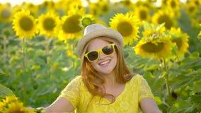 Девушка красоты с длинными красными волосами стоит в желтом поле солнцецвета счастливая женщина outdoors teen подросток Сторона П акции видеоматериалы