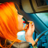 Девушка крася ее губы делая состав пока управляющ автомобилем Стоковые Изображения