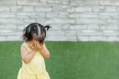 Девушка крупного плана азиатская принять ее руки со стороны и сыграть спрятанный с кто-то на поле травы и текстурированной кирпич стоковые фотографии rf